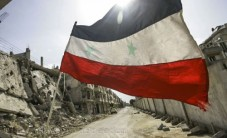 A Syrian flag flutters outside a militar
